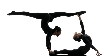 contortionist: two women contortionist practicing gymnastic yoga in silhouette   on white background Stock Photo