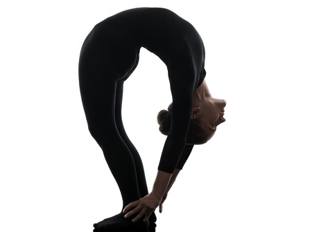one caucasian woman contortionist practicing gymnastic yoga  in silhouette   on white background photo