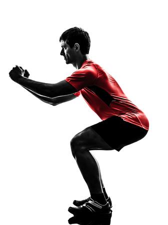 ejercicio aer�bico: un hombre que ejercita entrenamiento estocadas agazapado en silueta sobre fondo blanco