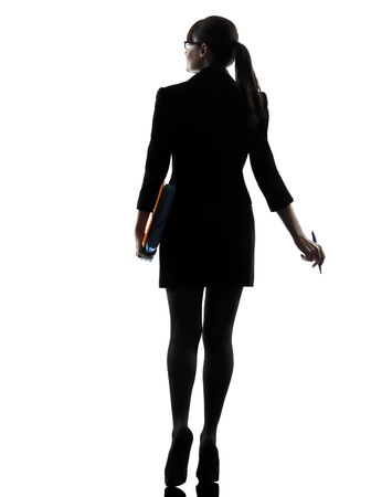 business woman standing: one business woman leaving holding folders files  silhouette studio isolated on white background Stock Photo