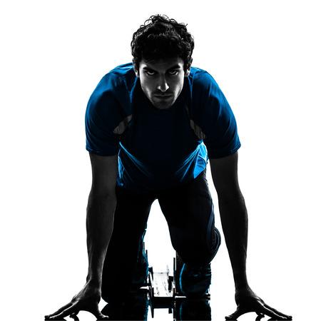 coureur: un homme caucasien coureur sprinter sur les starting blocks en studio silhouette isol� sur fond blanc Banque d'images