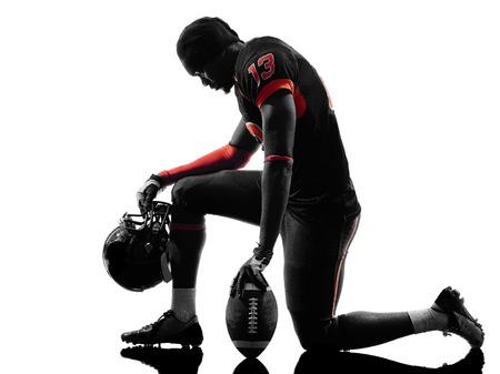 흰색 배경에 실루엣 그림자에 무릎을 꿇 한 미국의 축구 선수
