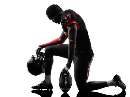 football player: one  american football player kneeling  in silhouette shadow on white background