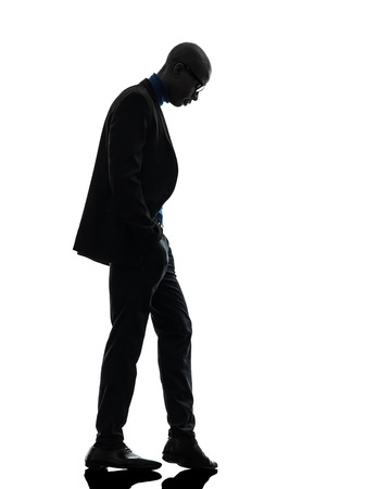 one african  black man standing looking down  in silhouette studio on white background photo