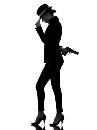women with guns: one stylish caucasian woman in suit holding gun in silhouette  on white background