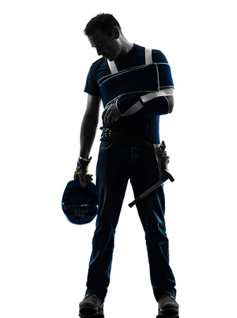 one injured manual worker man with injury brace despair in silhouette on white background photo