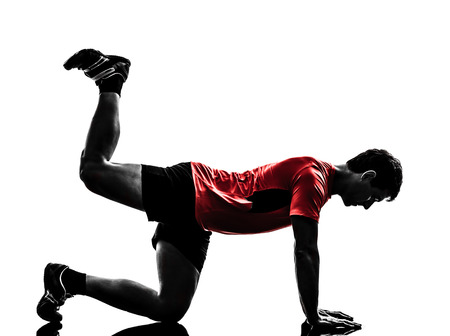 plank position: one man exercising fitness workout plank position in silhouette on white background