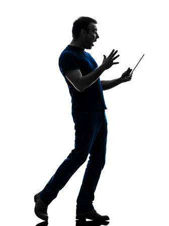 one caucasian man holding digital tablet  surprised in silhouette on white background