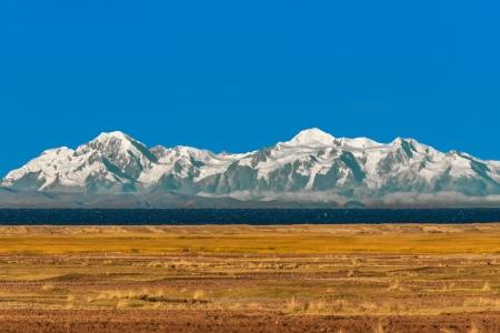Bolivian mountains from peruvian Andes Titicaca Lake at Puno Peru photo