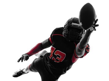 american football player: one  american football player catching ball   in silhouette shadow on white background