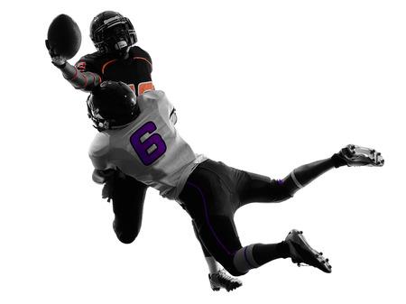 jugadores de futbol: dos jugadores de f�tbol americano abordan en sombra de la silueta en el fondo blanco Foto de archivo
