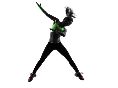 one caucasian woman exercising fitness zumba dancing jumping in silhouette  on white background Фото со стока