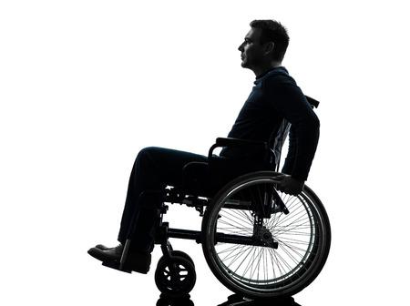persona en silla de ruedas: ver un lado el hombre discapacitado grave en estudio de la silueta sobre fondo blanco Foto de archivo