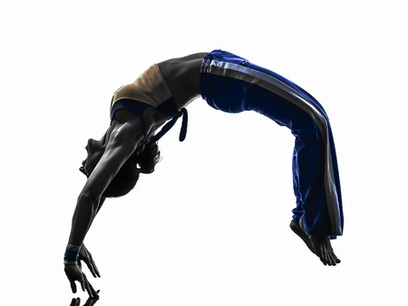 one caucasian woman capoiera dancer dancing backflip in silhouette studio on white background photo