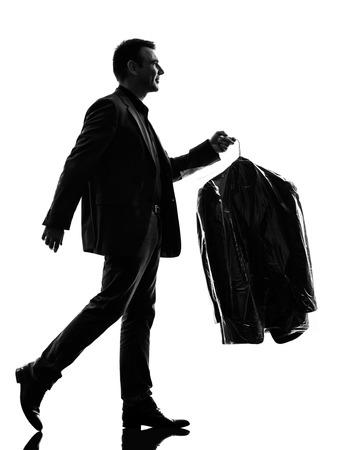 limpiadores: un hombre de negocios cauc�sico que sostiene la ropa limpia en seco en la silueta en el fondo blanco
