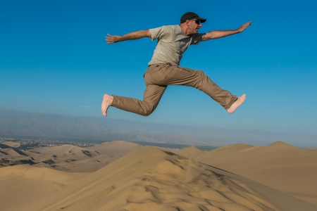 man jumping in the desert in the peruvian coast at Ica Peru photo