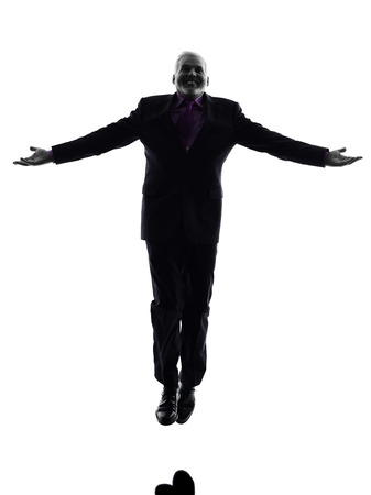 senior business man: One Caucasian Senior Business Man jumping arms outstretched Silhouette White Background