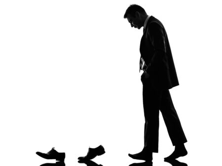 one caucasian business man walking behind his shoes   in silhouette  on white  photo