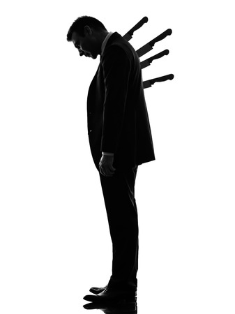 one caucasian business man Stabbed in the Back in silhouette  on white background photo