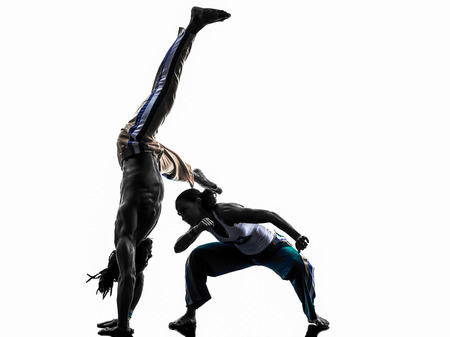 two people couple capoeira dancers dancing in silhouette studio isolated on white background photo
