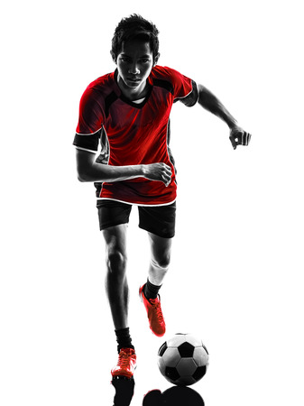 one asian soccer player young man dribbling in silhouette isolated white background photo