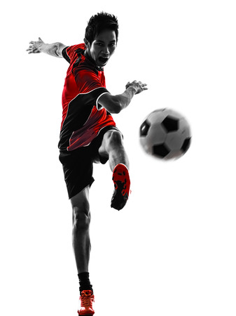 isolated on the white background: one asian soccer player young man kicking in silhouette isolated white background