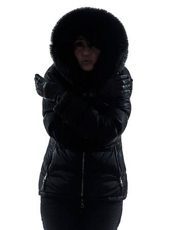 one woman: one woman in winter coat freezing cold silhouette on white background
