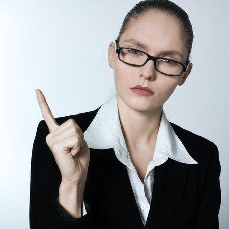strict: studio shot portrait of one beautiful business strict nanny teacher woman pointing Stock Photo
