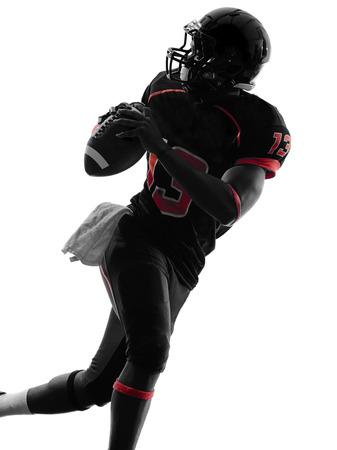 pelotas de futbol: un estadounidense retrato futbolista quarterback en la sombra de la silueta en el fondo blanco Foto de archivo