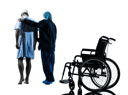 one injured man walking away from wheelchair with nurse in silhouette studio on white background photo