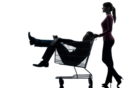 one caucasian couple woman with man sitting in shopping cart  in silhouette studio  photo