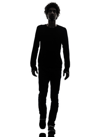 one african handsome young man walking in silhouette studio isolated on white background photo