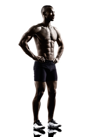 one young african muscular build man standing topless silhouette  isolated on white background photo