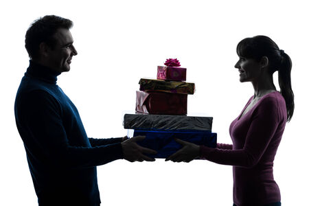 one caucasian couple woman man offering christmas gifts in silhouette studio isolated on white background photo