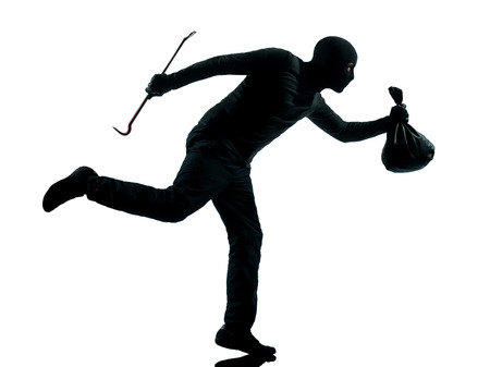 looting: thief criminal running in silhouette studio isolated on white background in silhouette studio isolated on white background