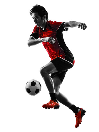 dribbling: one asian soccer player young man dribbling in silhouette isolated white background