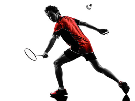 one asian badminton player young man  in silhouette isolated white background photo