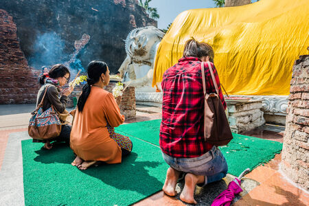 Bangkok, Thailand - December 29, 2013  people praying to the reclining buddha statue at Wat Yai Chaimongkol Ayutthaya in Bangkok, Thailand on december 29th, 2013