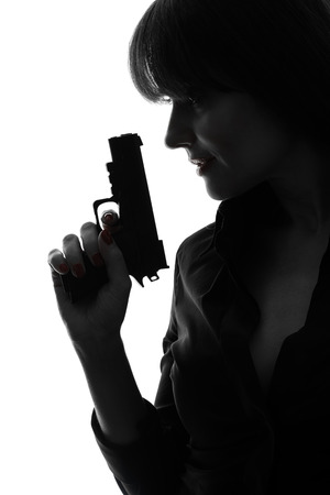 one woman: one caucasian sexy detective woman holding aiming gun in silhouette studio isolated on white background