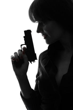 mujer con pistola: una mujer caucásica detective sexy sosteniendo la pistola apuntando en la silueta del estudio aislada en el fondo blanco
