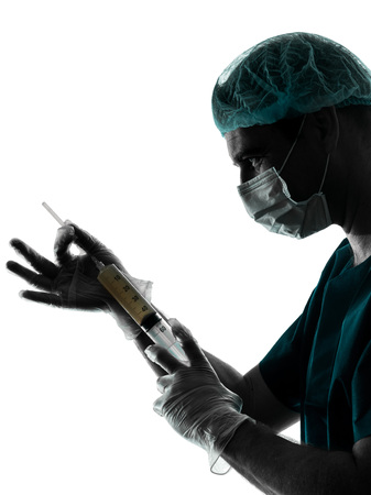 anesthetist: one caucasian doctor surgeon Anesthetist man holding surgery needle silhouette isolated on white background