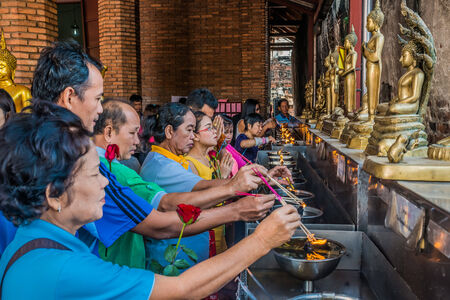 Bangkok, Thailand - December 29, 2013: people lighting incense at Wat Yai Chaimongkol Ayutthaya in Bangkok, Thailand on december 29th, 2013