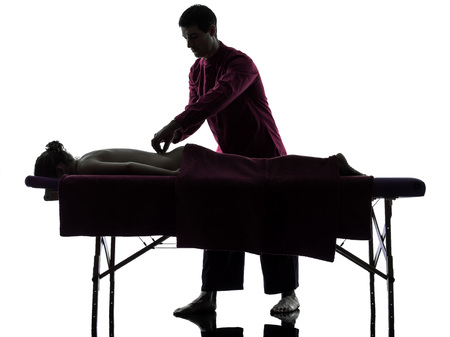 massage table: man woman back massage in silhouette studio on white background
