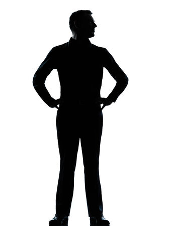 man looking out: one caucasian business man silhouette standing hands on hips Full length in studio isolated on white background