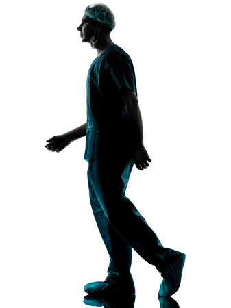 one caucasian man doctor surgeon medical worker walking silhouette isolated on white background photo