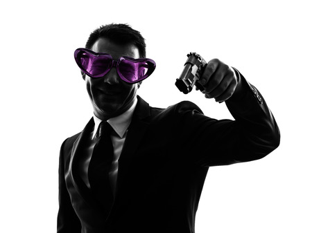 one caucasian business man with heart shaped glasses aiming in silhouette on white background photo