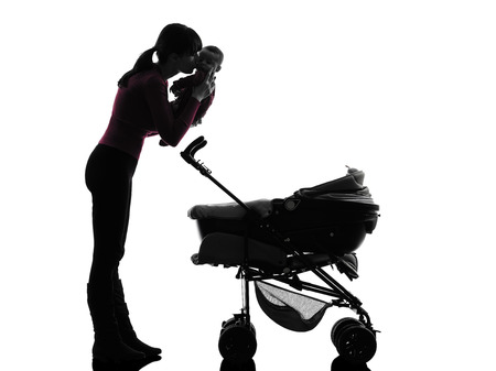one caucasian woman prams holding baby kissing silhouette on white background photo