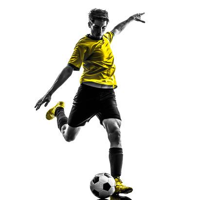 patada: hombre joven jugador de f�tbol del f�tbol brasile�o patadas en estudio de la silueta sobre fondo blanco