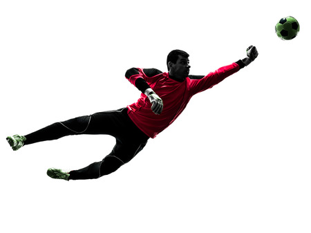 one caucasian soccer player goalkeeper man punching ball in silhouette isolated white background photo