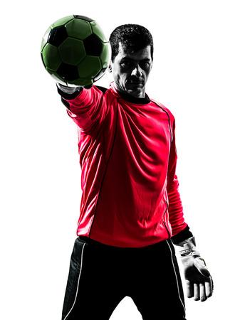 portero: un caucásico futbolista portero hombre de pie pelota parada con una mano en la silueta aislado fondo blanco Foto de archivo